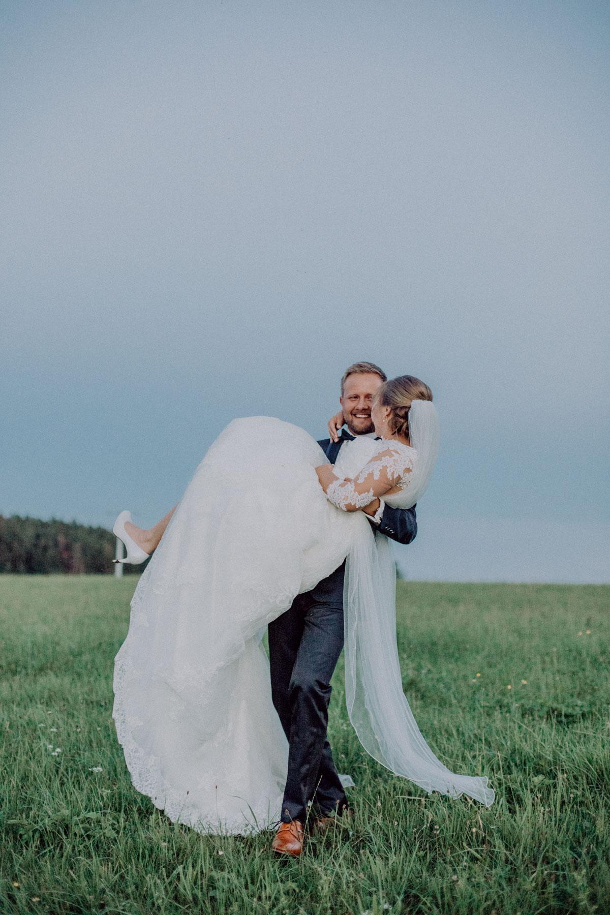 Brautshooting Bräutigam trägt Braut Hochzeitsfotograf