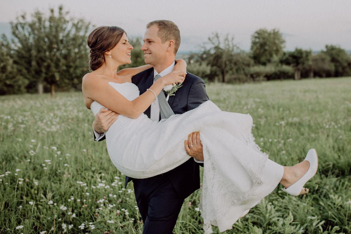 Groom carries Bride